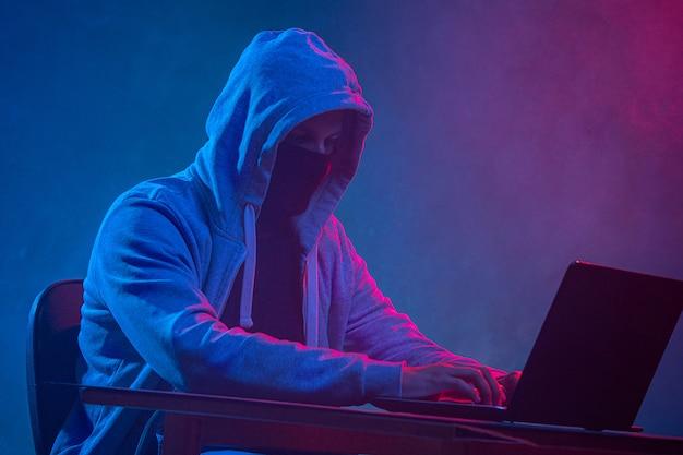 Hooded computerhakker die informatie met laptop steelt