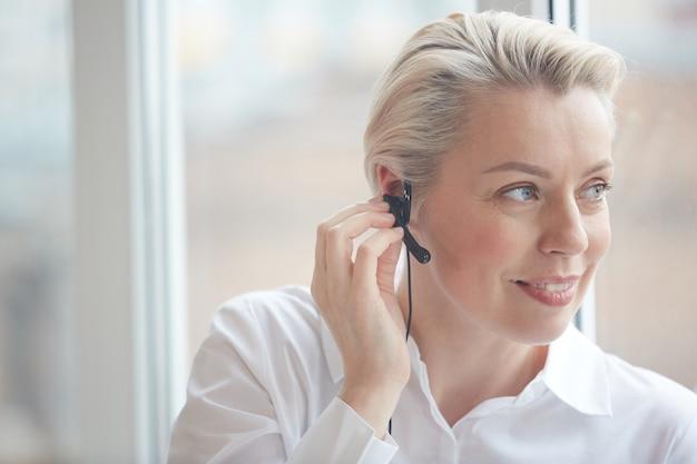 Hoofd en schouders portret van glimlachende zakenvrouw hoofdtelefoon dragen en raam kijken tijdens het werken in callcenter