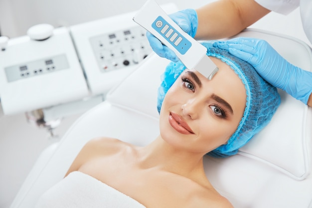 Hoofd en schouders van vrouw liggend op de bank in blauwe dop in cosmetologische kliniek en camera te kijken. de arts dient blauwe handschoenen in die ultrasone scraber dichtbij haar gezicht houden