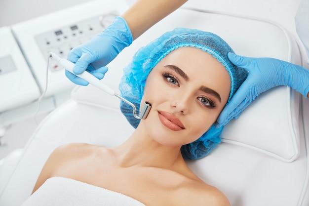 Hoofd en schouders van vrouw liggend op de bank in blauwe dop in cosmetologische kliniek en camera te kijken. de arts dient blauwe handschoenen in met elektrode voor galvanisatie in de buurt van haar gezicht