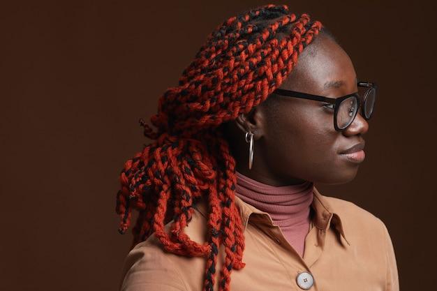 Hoofd en schouders zijaanzicht portret van hedendaagse afro-amerikaanse vrouw met gevlochten haar wegkijken terwijl poseren tegen donkere bruine achtergrond in studio, kopieer ruimte