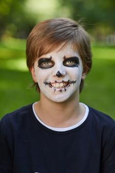 Hoofd en schoudersportret van glimlachende tiener die halloween-kostuum met schmink draagt en terwijl in openlucht stelt