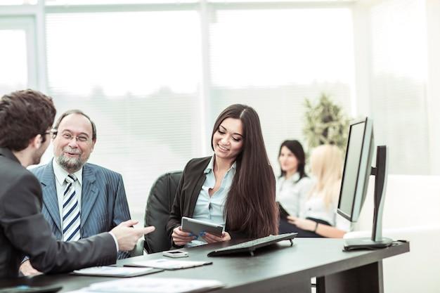 Hoofd en zakelijk team om financiële documenten voor de werkplek te bespreken.
