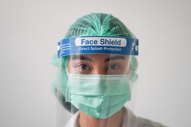 Hoofd geschoten beeld van medisch personeel dat een pak met persoonlijke beschermingsmiddelen (pbm) draagt ter bescherming van de nieuwe pandemie van het coronavirus (covid-19)