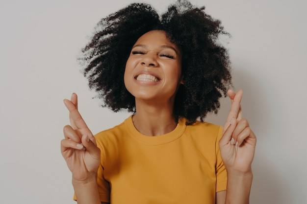 Hoofd geschoten glimlachend mooi afrikaans amerikaans meisje met gesloten ogen die vingers kruisen die veel geluk wensen, hoopvolle vrouw die om wens vraagt die uitkomt, geloof in bijgeloof geïsoleerd op witte achtergrond