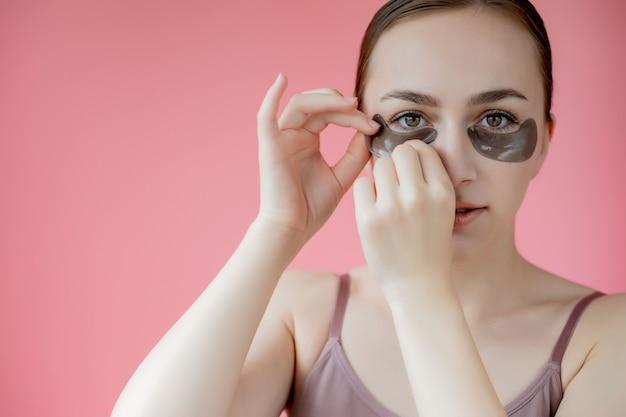 Hoofd geschoten portret close-up lachende jonge vrouw met onder de ogen hydraterende patches masker kijken camera genieten van huidverzorging procedure.