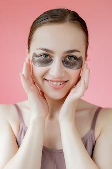 Hoofd geschoten portret close-up lachende jonge vrouw met onder de ogen hydraterende patches masker kijken naar camera genieten van huidverzorging procedure