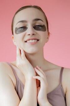 Hoofd geschoten portret close-up lachende jonge vrouw met onder de ogen hydraterende patches masker kijken naar camera genieten van huidverzorging procedure.