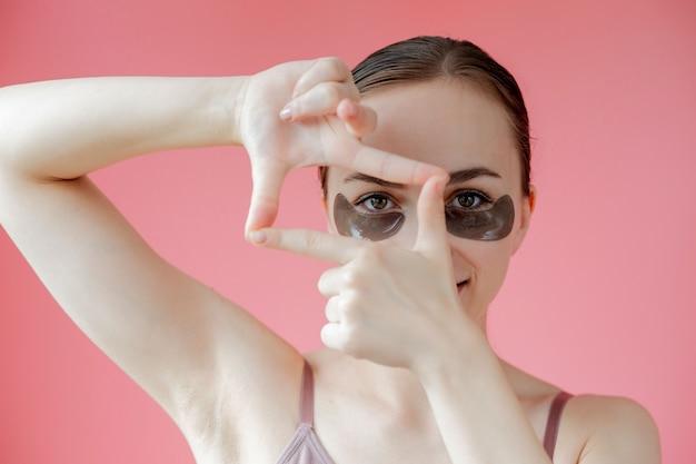 Hoofd geschoten portret close-up lachende jonge vrouw met onder de ogen hydraterende patches masker kijken