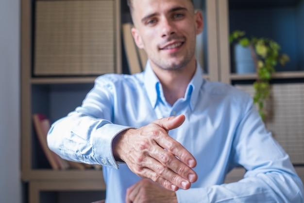 Hoofd geschoten portret lachende zakenman met een bril die de hand uitsteekt voor handdruk op de camera, vriendelijke hr-manager die de kandidaat begroet tijdens het interview, een deal aanbiedt, de klant verwelkomt tijdens de vergadering
