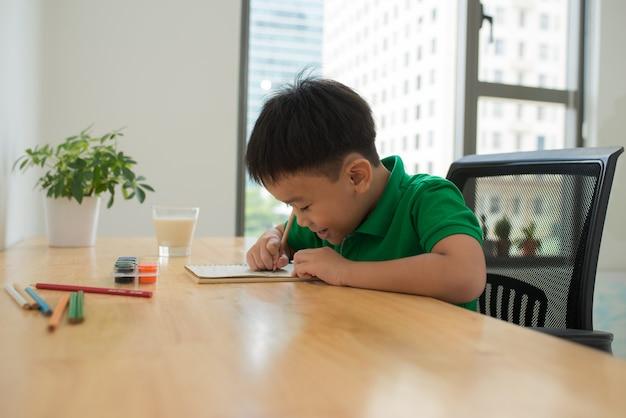 Hoofd geschoten portret van een gelukkig aziatisch schattig kind dat thuis huiswerk maakt met een glimlach.