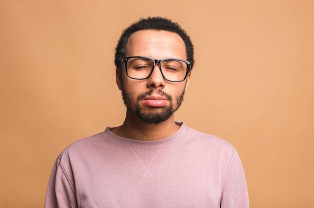 Hoofd geschoten studio portret over beige blanco geïsoleerde trieste man voelt zich gefrustreerd en ongelukkig met een gebroken hart persoonlijke problemen