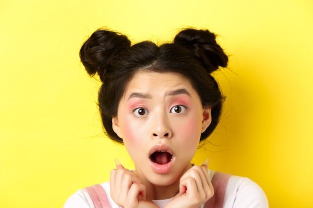 Hoofd geschoten van geschokt aziatisch meisje met haarknoppen en glamour make-up, open mond en kijken geschrokken naar camera, staande tegen geel
