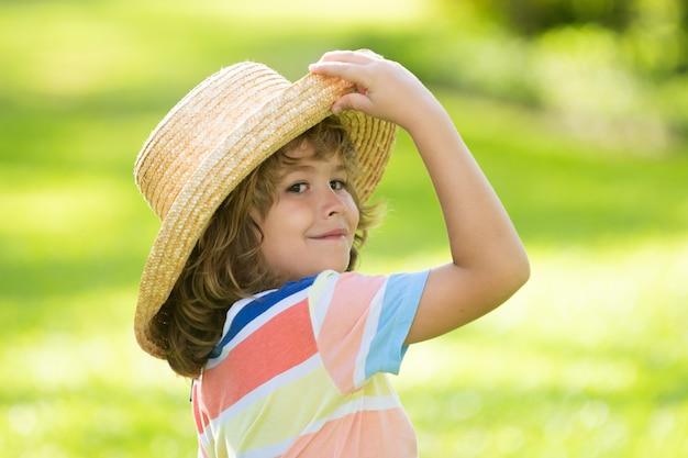 Hoofd geschoten van zomerkind in strohoed. kinderen gezicht, kleine jongen portret.