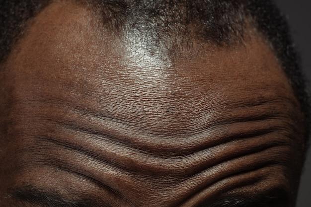 Hoofd, gezicht. gedetailleerde textuur van de menselijke huid. close-up shot van jonge afro-amerikaanse mannelijke lichaam. huidverzorging, lichaamsverzorging, gezondheidszorg, hygiëne en geneeskundeconcept. ziet er mooi en verzorgd uit. dermatologie.