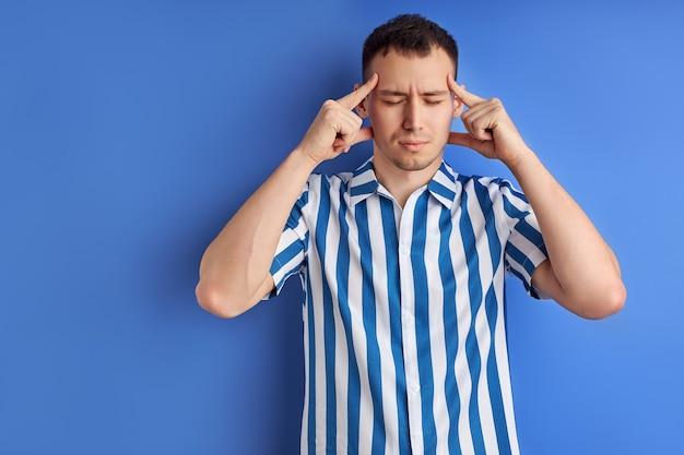 Hoofd is explosieve sterke migraine worstelen knappe jonge blanke man met sterke pijngrimas