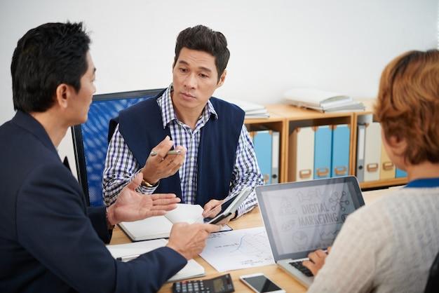 Hoofd marketingafdeling luistert naar ideeën van collega's tijdens vergadering