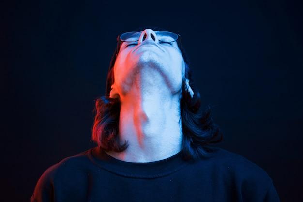 Hoofd omhoog. studio opname in donkere studio met neonlicht. portret van ernstige man