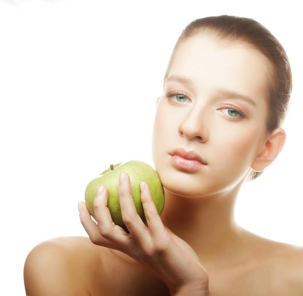 Hoofd schot van vrouw met groene appel op wit