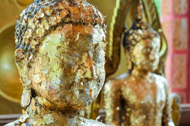 Hoofd van boeddhabeeld met vergulden blad