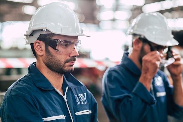 Hoofd van de ingenieur, het portret van de arbeidersleider zelfvertrouwen en professionele uitstraling met een veiligheidsbril en een witte helm.