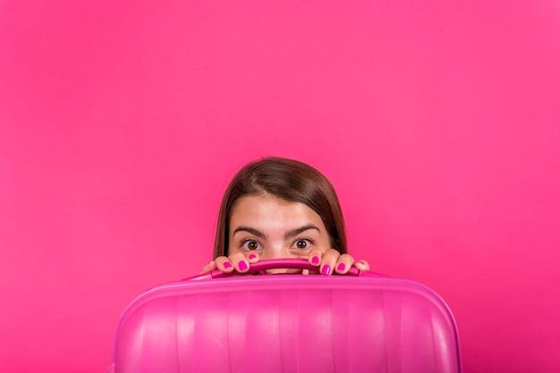 Hoofd van de vrouw verstopt achter een roze koffer
