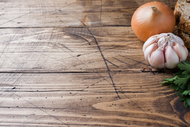Hoofd van knoflook, ui en peterselie op houten tafel.