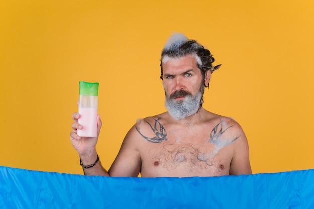 Hoofd wassen man met shampoofles onder douche lichaam wassen bebaarde man douchen haarverzorging