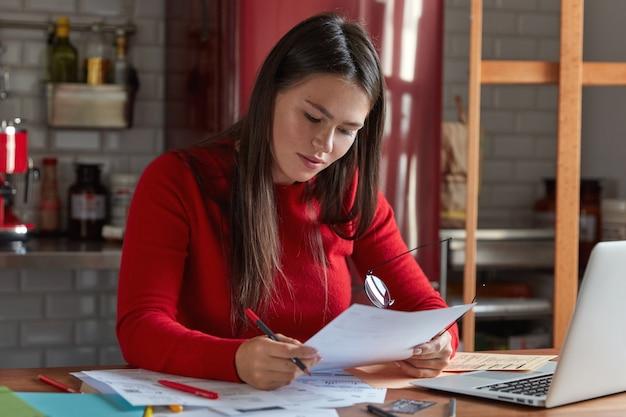 Hoofdarchitect vrouw werkt met documentatie, bevestigt project, houdt papier en bril in handen, poseert in de keuken, chats met marketingexperts op laptopcomputer. mensen en carrièreconcept