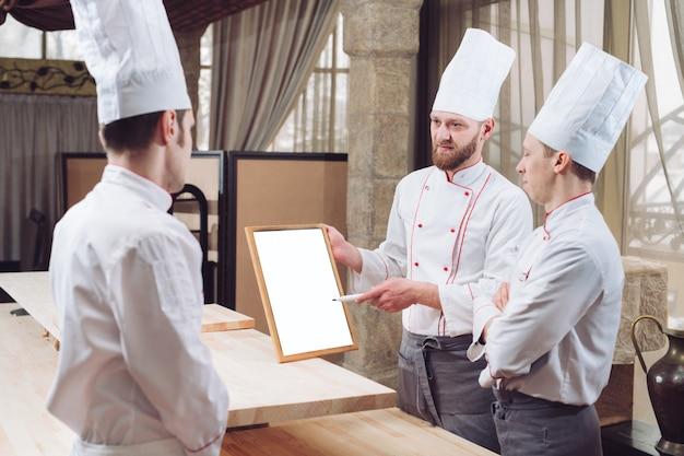 Hoofdchef en zijn personeel in keuken.