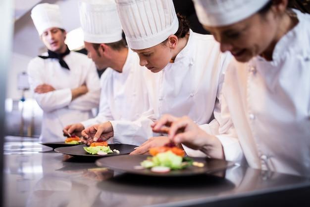 Hoofdchef-kok die andere chef-kok overzien die schotel voorbereiden