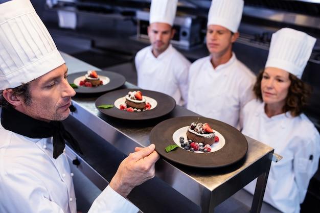 Hoofdchef-kok die dessertplaten inspecteren bij ordepost