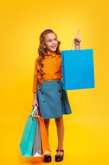 Hoofdgedeelte van lachende stijlvolle meisje in vrijetijdskleding met kleurrijke boodschappentassen in handen die omhoog wijst terwijl je staat