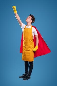 Hoofdgedeelte van vastberaden jonge man in rode superheld cape en schort met latex handschoenen staan met opgeheven arm