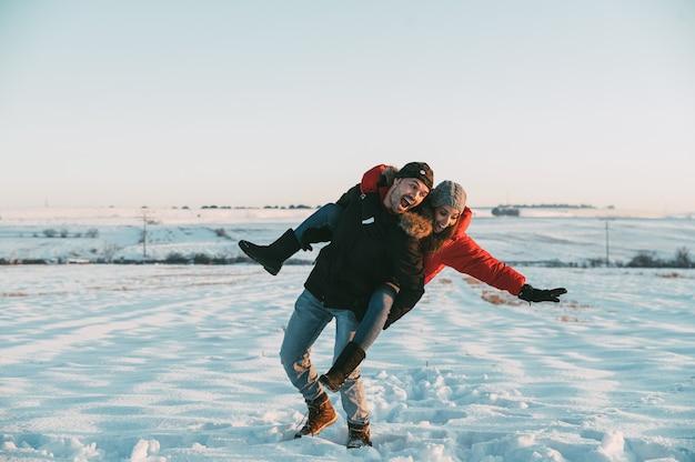 Hoofdgedeelte van vrolijke man die meeliften rit en vallen en lachen met vriendin in besneeuwde landschap