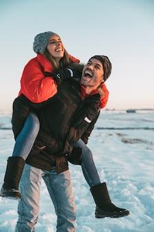 Hoofdgedeelte van vrolijke man die op de rug rit geven aan lachende vriendin in besneeuwde landschap
