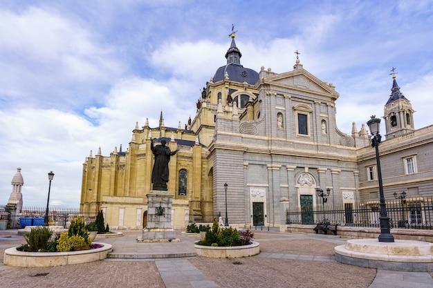 Hoofdingang van de almudena-kathedraal in madrid, blauwe hemel met wolken. spanje.
