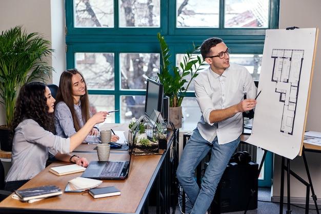 Hoofdingenieur die over nieuw creatief idee in de bouwplannen spreekt terwijl twee vrouwelijke medewerker die in het notitieboekje in het moderne bureau opmerken.