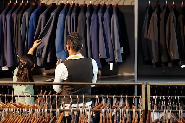 Hoofdkleermaker en ateliermanager die de kwaliteit controleert van op maat gemaakte jassen die aan de rail hangen, zicht vanaf de achterkant