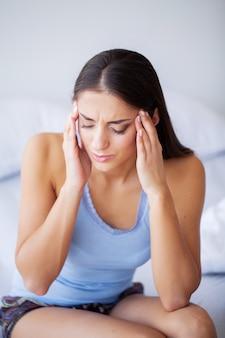 Hoofdpijn. aantrekkelijke jonge vrouw wakker op haar bed op zoek ongelukkig en zich ziek voelen.