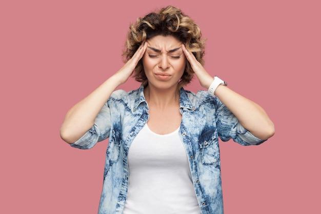 Hoofdpijn, denken of verwarring. portret van een trieste jonge vrouw met krullend haar in een casual blauw shirt dat haar pijnlijke hoofd met gesloten ogen vasthoudt. indoor studio-opname geïsoleerd op roze achtergrond