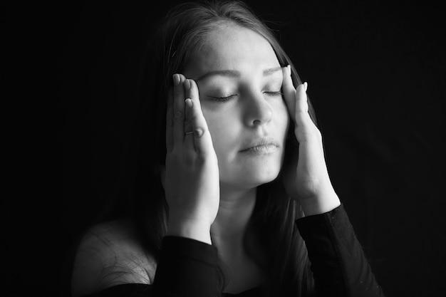 Hoofdpijn en depressie, zwart en wit portret van een vermoeide vrouw