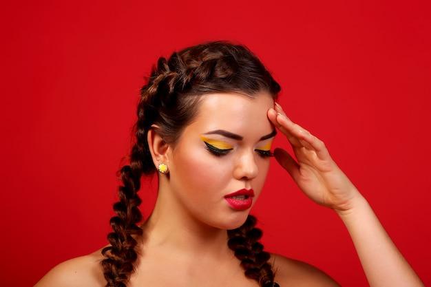 Hoofdpijn - jonge vrouw die zijn hoofd op een rode muur houdt