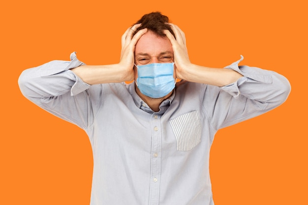 Hoofdpijn of verwarring. portret van een droevige of boze jonge arbeider met een chirurgisch medisch masker dat staat en zijn pijnlijke hoofd vasthoudt, denkend of volhardend. indoor studio-opname geïsoleerd, oranje achtergrond.
