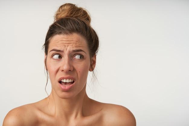 Hoofdportret portret van geschokt gefrustreerde jonge vrouw met knot kapsel, opzij kijkend met een verbaasde grimas, geïsoleerd op wit