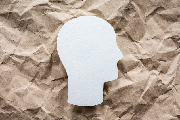 Hoofdsymbool op verfrommeld papier achtergrond, geestelijke gezondheid en psychologie idee
