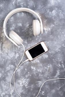 Hoofdtelefoon en een telefoon op een stenen achtergrond. klaar om naar muziek te luisteren.