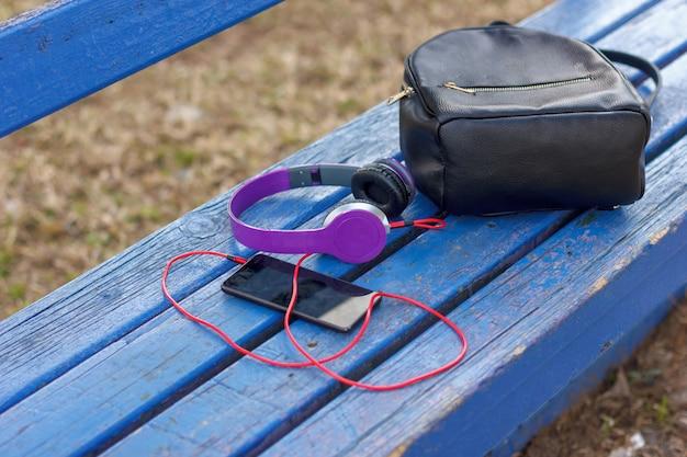 Hoofdtelefoon met een smartphone en een zwarte rugzak op een blauwe bank in het park