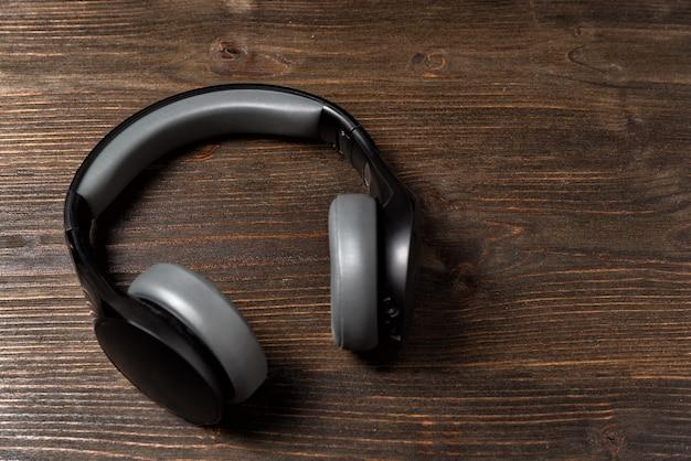 Hoofdtelefoon op donkere houten achtergrond. zwarte koptelefoon, bovenaanzicht