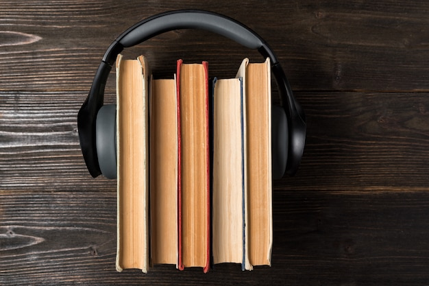 Hoofdtelefoon versleten op een stapel oude boeken op houten achtergrond. favoriete audioboekconcept. bovenaanzicht
